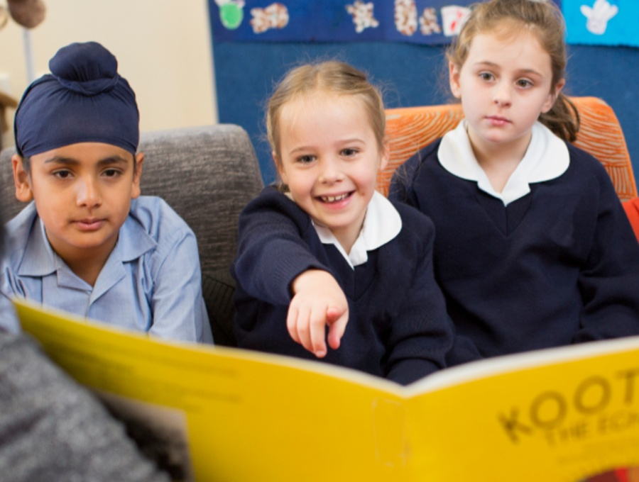 Young students reading a book together