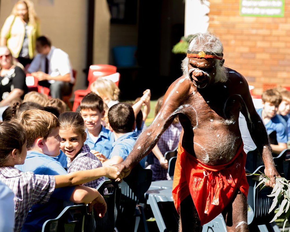 Child and Aboriginal Elder shaking hands at a cultural ceremony