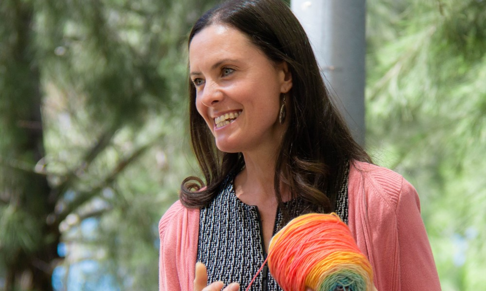 A Narragunnawali staff member smiles, holding a ball of yarn.